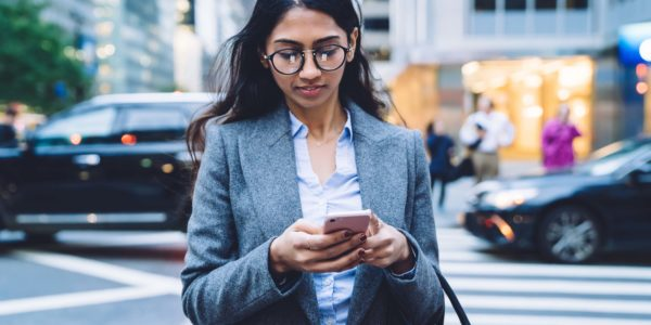 Beautiful ethni business woman in glasses and gray jacket browsing in mobile phone while crossing road in New York City